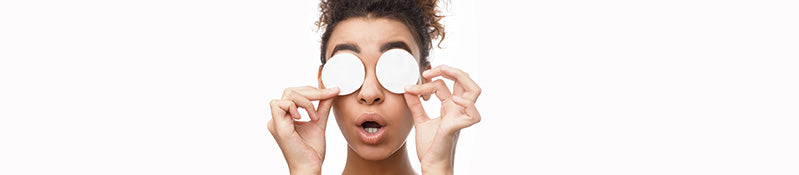 girl holding cleansing pads over eyes