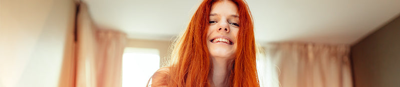 girl with red hair and curtains in background