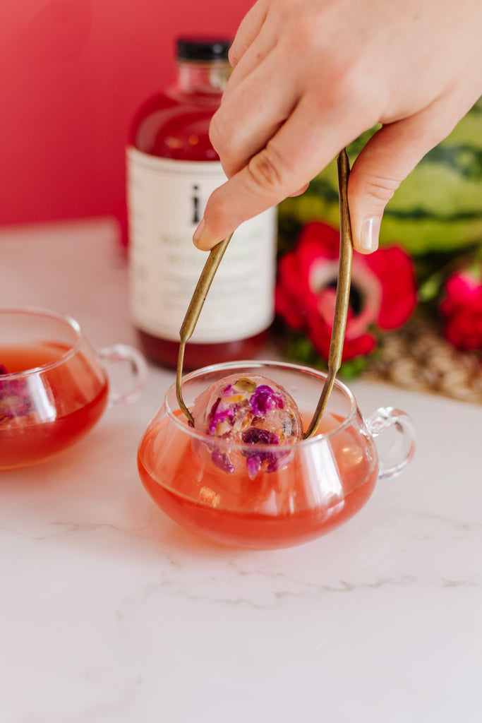 A tea inspired cocktail with Iconic Watermelon Rose Tonic and Juneshine Rose and a delicate rose petal super cube.