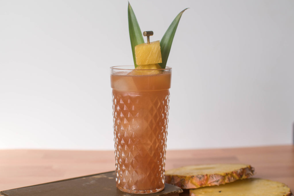 A tiki-like cocktail made with Iconic Mesquite Date, silver rum, and pineapple juice