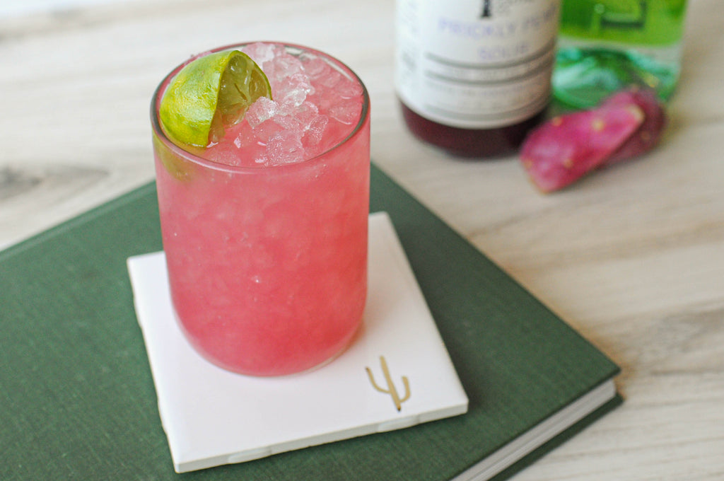 Inspired by Brazil's national drink, this Caipirinha is made with Cachaca, fresh limes, and Iconic Prickly Pear Sour for extra color