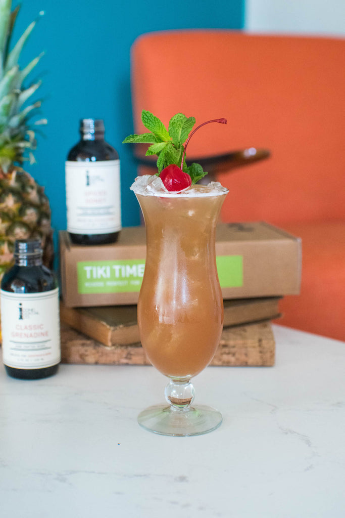 Make a Singapore Sling cocktail with Iconic Mixers for an ultimate Tiki experience! Find all the right tiki flavors in one place with the Iconic Tiki Spirit Pack.