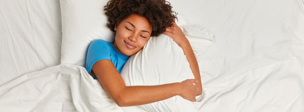 Woman sleeping soundly hugging one of her pillows