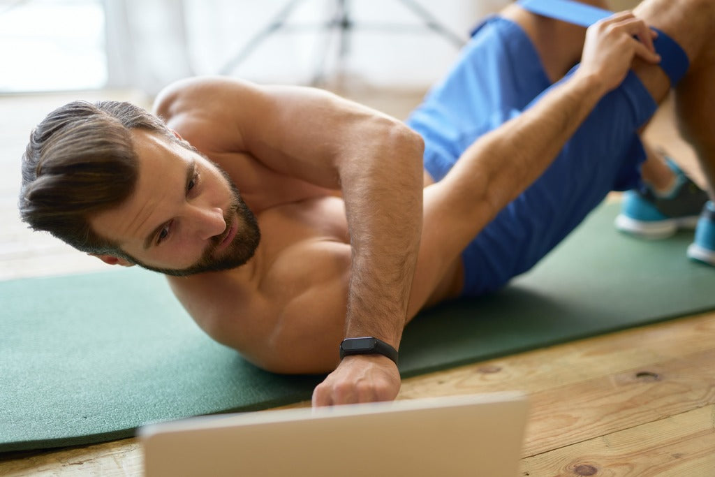 athletic-young-man-using-laptop-during-home-workout