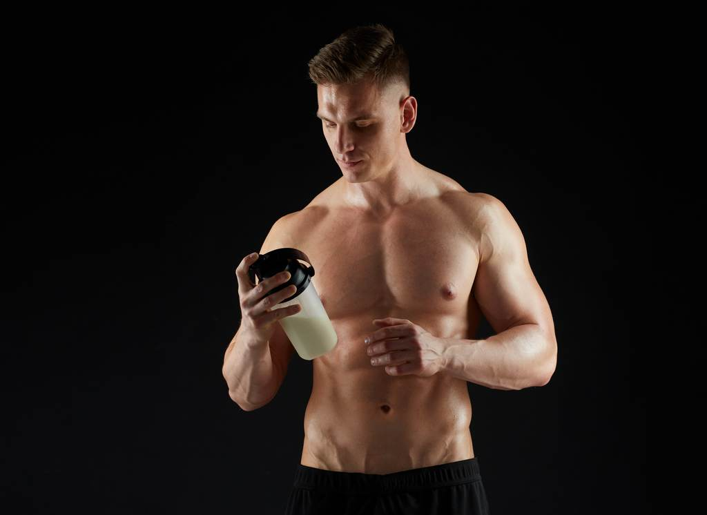 Young body builder taking supplements