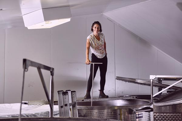 Susuro's Nikki Palun standing on top of wine vat