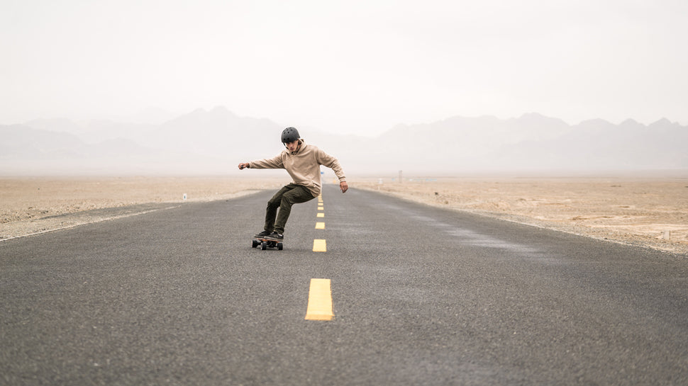 A Man Riding LycaonBoard Electric Skatebaord on a braod road