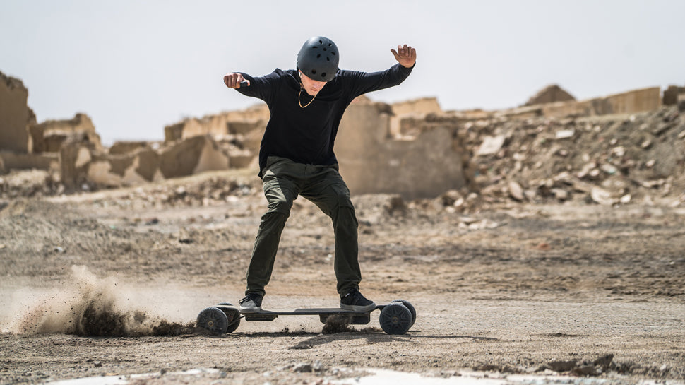 A man in black shirt riding the LycaonBoard Off Road Electric Skateboard