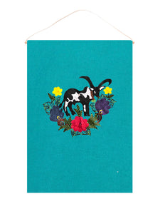 Cow wall hanging on blue linen