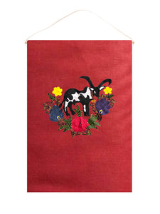 Cow wall hanging on red linen