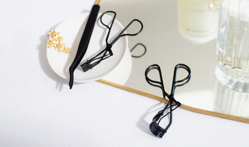 Matte black Lithe Lash Applicator on a stylish plate, next to black Lithe Mini Lash Curler and Lithe Lash Curler on a white and light grey back ground, resting partially on a stylish clear and clean mirror