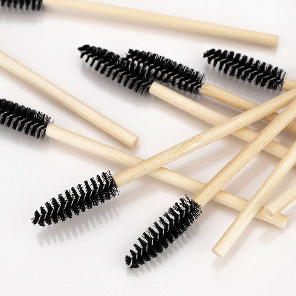 A pile of spoolies with a bamboo handle and black brush head, pointing in different directions