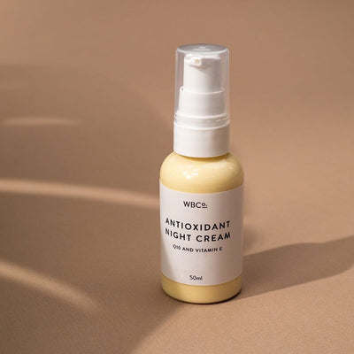 A bottle of night cream against a pale brown background, next to shadows of plant leaves