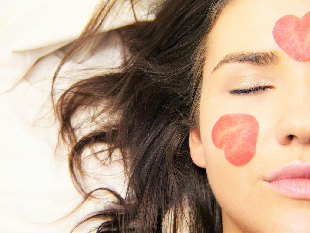 Brunette with beautiful skin filled with heart-shaped kisses