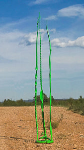 A tall green hand forged steel sculpture with three tall individual pieces that are attached to a spiral base.