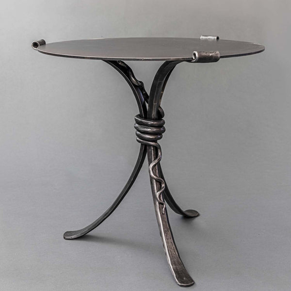 A three legged hand forged wrought iron table featuring a hand forged rattlesnake wrapped around the center of the table legs.