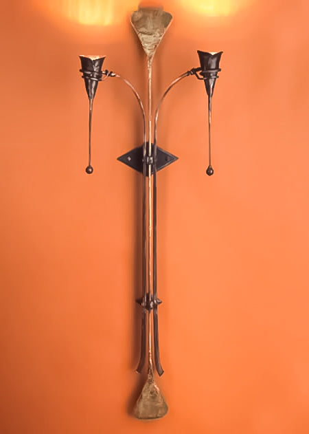 An oversized wrought iron and bronze wall sconce featuring two calla lily light bulbs that shine upwards.