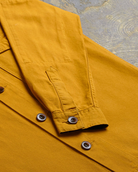 Close-up of cuff and sleeve of golden button-down Uskees shirt with focus on corozo buttons.