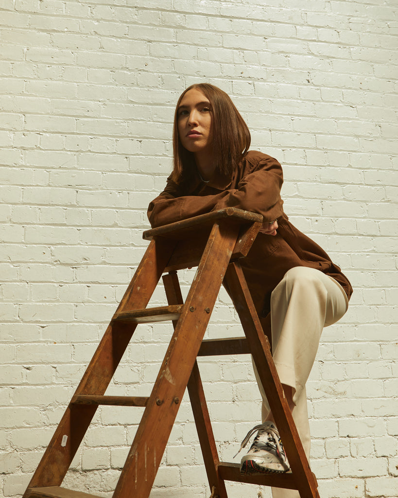 Woman on stepladder wearing brown uskees jacket.