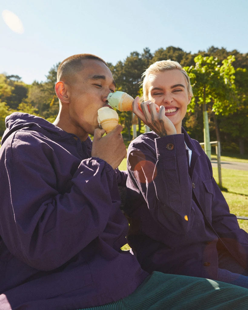 Couple sat on bench wearing purple Uskees tops eating ice cream.