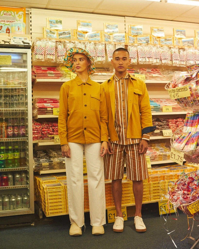 Couple wearing dull gold Uskees tops in seaside gift shop.