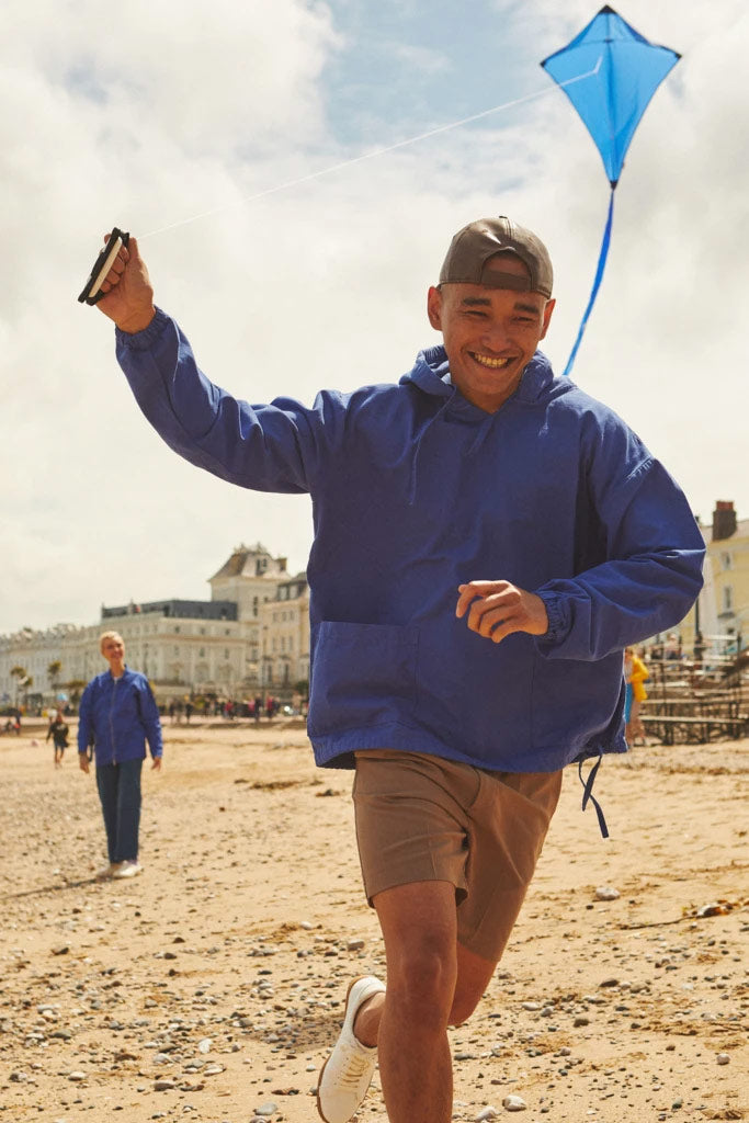 Man wearing Uskees smock while flying kite on Welsh beach.