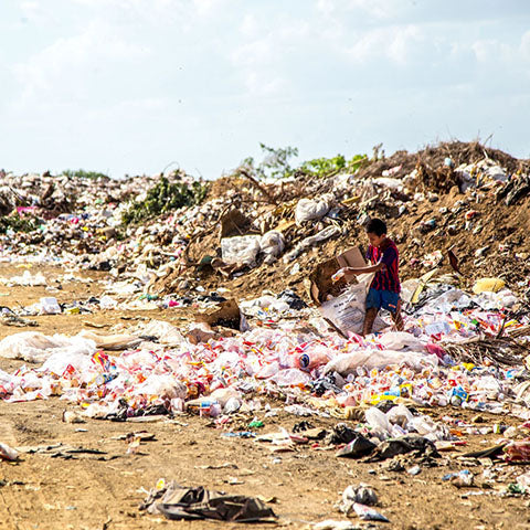 Boy walking through landfill site surrounded by waste.