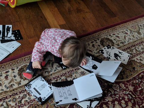 toddler looking at black and white board book