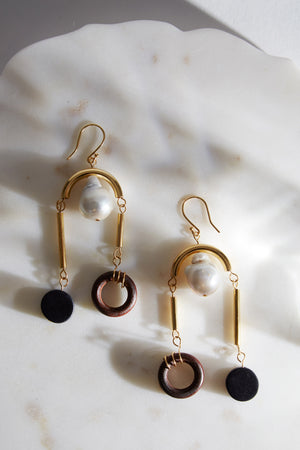 The gold-plated and baroque peal MLE Scala earrings on marble surface