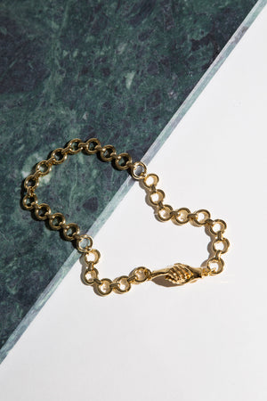 The gold-plated MLE Gentlewoman's Agreement Necklace on green marble surface