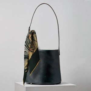 The MLE silk twill Marbré scarf in dark green pine with the 706 Bucket Bag Handbag