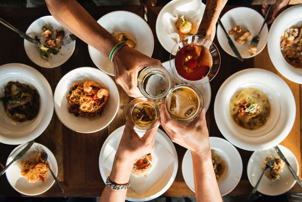 hands toasting above food in white dishes