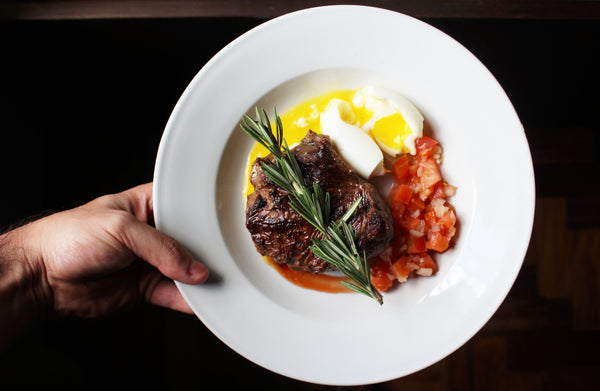 seared steak and poached egg in white dish