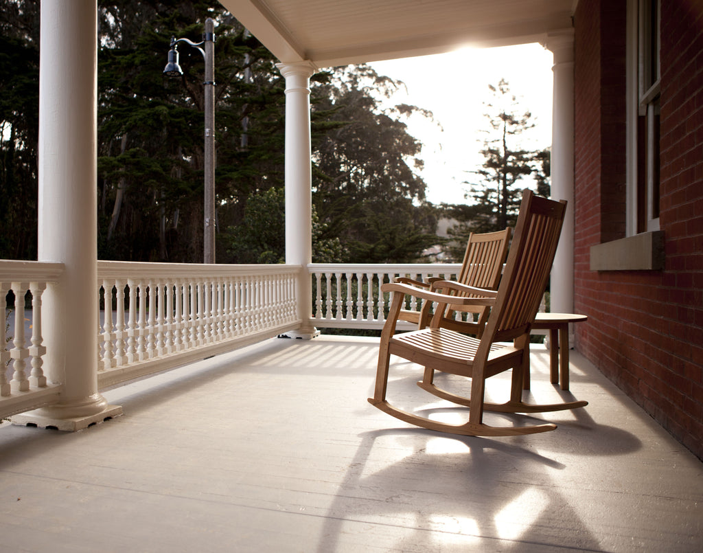 Two rocking chairs sit on the porch of the Inn at Presidio as the sun sets behind the trees.