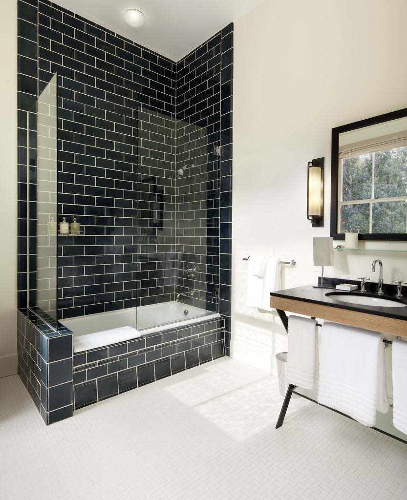 A white tile bathroom that features a glossy black tile shower, bathtub, and a stylish sink with a black countertop.