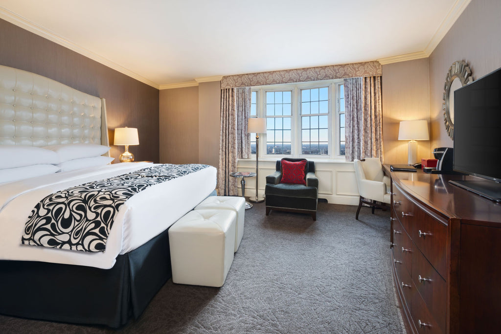 The interior of a guest room at The Pfister Hotel featuring a king-sized bed and elegant furnishings.