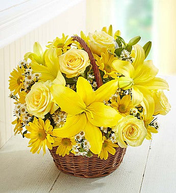 A Keepsake wicker basket filled with yellow flowers such as: Asiatic lilies, roses, daisies and more.