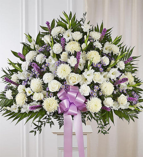 In this elegant basket are white flowers and a touch of lavender flowers that will help to express your most heartfelt sympathies