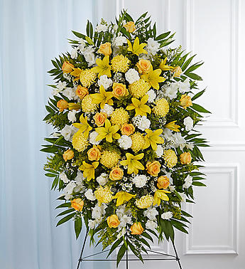 A standing spray on an easel filled with white carnations, yellow daisy poms, yellow roses, yellow mums, lush greens, and more.