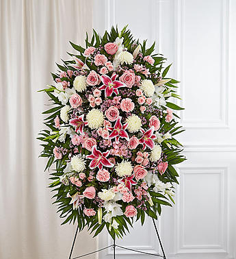Express your most heartfelt condolences with this beautiful hand arranged standing spray of pink and white flowers. The spray is filled with roses, lilies, alstroemeria, carnations, waxflower, mums, and more.