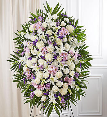 spray contains mums, roses, carnations, and more and are arranged in an oval shape.