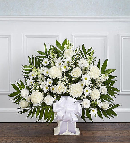 A beautiful sympathy floor basket filled with bright white flowers such as: Mums, Carnations, Roses, and more. Suitable for the funeral home.