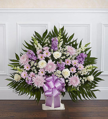 Sympathy basket is filled with lavender mums, white roses, lavender stock, lavender bow