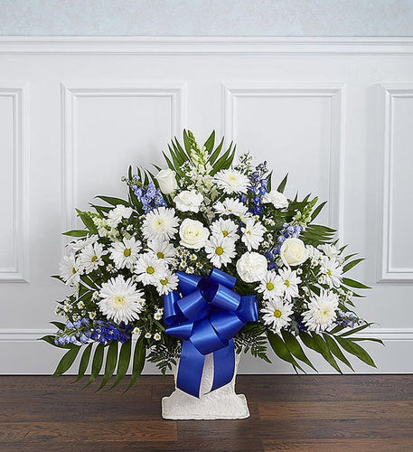 The basket includes: white roses, white mums, white lilies, white snapdragons, white carnations, blue delphinium, white Monte Casino, and a beautiful blue ribbon.