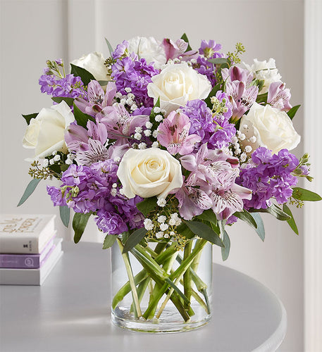beautiful mixture of white and lavender flowers, roses, alstroemeria, stock and more in a cylinder vase.