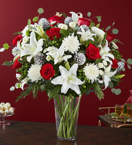 holiday vase arrangement of white oriental lilies, white football mums, red roses, holiday greens