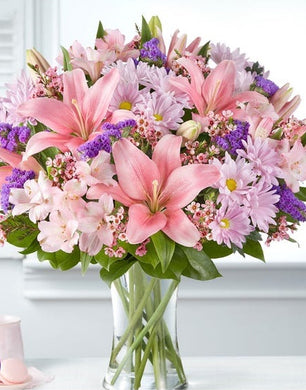 A vase of lilies, ,daisies, poms,alstroemeria, and more.