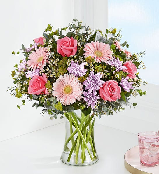Our fresh-from-the-garden bouquet is loosely gathered with pastel blooms inside a glass vase.