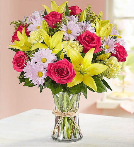 This rich vibrant bouquet delivers your sentiments to someone special and is a great way to express how you feel inside. This clear glass vase is filled with lilies, daisy poms, roses, and more.