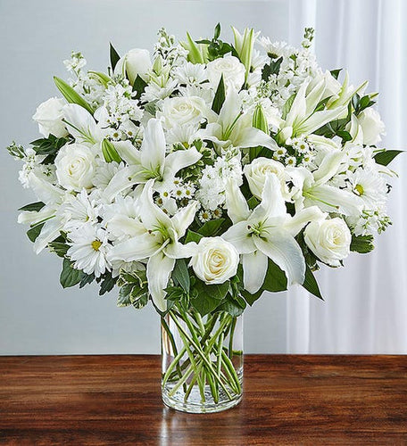 A brilliant pure white arrangement.  This floral vase is so striking with white lilies, white roses, white stock, and much more.